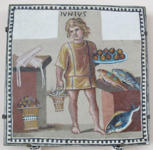 A boy holding a platter of fruits and a bucket of crab(?) in a kitchen with fish andsquid, on the June panel from a mosaic depicting the months (3rd century) CC Commons - creator Sailko